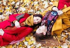 Deux belles jeunes femmes se trouvant sur les feuilles jaunes Image libre de droits