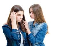 Deux belles jeunes femmes soulageant un un autre sur le fond blanc Photo libre de droits