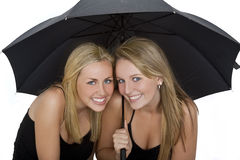 Deux belles jeunes femmes sous un parapluie Photographie stock libre de droits