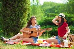 Deux belles jeunes femmes sur un pique-nique jouant une guitare Photo libre de droits