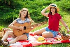 Deux belles jeunes femmes sur un pique-nique jouant une guitare et ayant l'amusement Images libres de droits