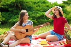 Deux belles jeunes femmes sur un pique-nique jouant une guitare et ayant l'amusement Photo stock