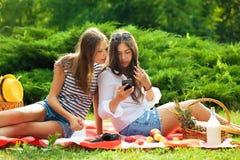 Deux belles jeunes femmes sur un pique-nique regardant l'écran de smartphone Image stock