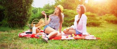 Deux belles jeunes filles à un pique-nique pendant l'été en parc mangeant des pommes et parler Photo libre de droits