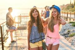 Deux belles jeunes filles ayant l'amusement au bord de la mer de soirée avec le groupe de leurs amis sur le fond Photos stock