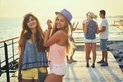 Deux belles jeunes filles ayant l'amusement au bord de la mer de soirée avec le groupe de leurs amis sur le fond Photographie stock libre de droits