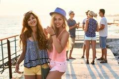 Deux belles jeunes filles ayant l'amusement au bord de la mer de soirée avec le groupe de leurs amis sur le fond Images stock