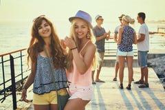 Deux belles jeunes filles ayant l'amusement au bord de la mer de soirée avec le groupe de leurs amis sur le fond modifié la tonal Photos libres de droits