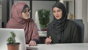 Deux belles jeunes filles dans les hijabs s'asseyent dans le bureau et discutent des programmes, affaires, dialogue, conversation banque de vidéos