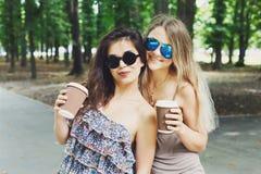 Deux belles jeunes filles de boho prennent le café dans le parc images stock