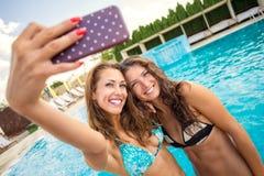 Deux belles jeunes filles prenant un selfie à une piscine Image stock