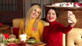Deux belles jeunes filles prennent des selfies se reposant dans un café, elles mangent des hamburgers banque de vidéos