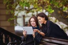 Deux belles jeunes filles regardent des photos sur votre comprimé, ayant une vie sociale et faisant des emplettes en ligne Images libres de droits