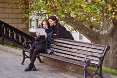Deux belles jeunes filles regardent des photos sur votre comprimé, ayant une vie sociale et faisant des emplettes en ligne Images stock