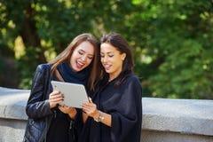 Deux belles jeunes filles regardent des photos sur votre comprimé, ayant une vie sociale et faisant des emplettes en ligne Photographie stock