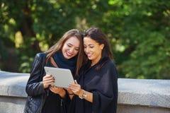 Deux belles jeunes filles regardent des photos sur votre comprimé, ayant une vie sociale et faisant des emplettes en ligne Photographie stock libre de droits