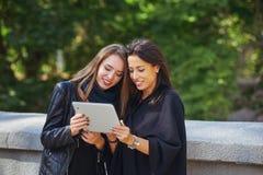 Deux belles jeunes filles regardent des photos sur votre comprimé, ayant une vie sociale et faisant des emplettes en ligne Photos stock