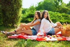 Deux belles jeunes filles s'asseyent sur un pique-nique d'été en parc Photos libres de droits