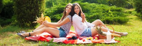 Deux belles jeunes filles s'asseyent sur un pique-nique d'été en parc Photo stock