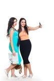 Deux belles jeunes filles sur un voyage allant de fond blanc Photo libre de droits