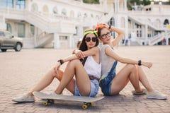 Deux belles jeunes filles sur une planche à roulettes dans la ville Image stock