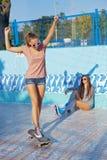Deux belles jeunes filles utilisant des lunettes de soleil dans un regroupement vide Images libres de droits