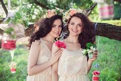 Deux belles jeunes soeurs de boho avec des fleurs Photo libre de droits