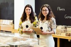 Deux belles jeunes vendeuses regardant l'appareil-photo tout en faisant l'inventaire dans le magasin organique Photo libre de droits
