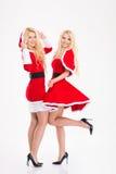 Deux belles jumelles blondes de soeurs dans des costumes du père noël Photographie stock