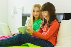Deux belles petites soeurs s'asseyant sur le lit et le jeu avec une Tablette ou un ordinateur portable Photographie stock libre de droits