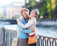 Deux belles rire et étreintes de filles dans la ville Photo libre de droits