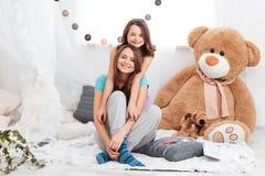 Deux belles soeurs de sourire s'asseyant ensemble Images stock
