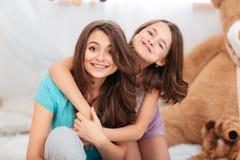 Deux belles soeurs heureuses s'asseyant et étreignant à la maison Images libres de droits