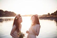 Deux belles soeurs riantes dans les rayons du coucher du soleil Photo libre de droits