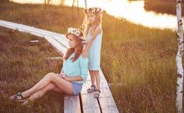 Deux belles soeurs se tenant dans la perspective d'un beau paysage, promenade sur le champ près d'un étang au coucher du soleil Photos stock