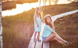 Deux belles soeurs se tenant dans la perspective d'un beau paysage, promenade sur le champ près d'un étang au coucher du soleil Photographie stock