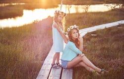 Deux belles soeurs se tenant dans la perspective d'un beau paysage, promenade sur le champ près d'un étang au coucher du soleil Photographie stock libre de droits