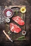 Deux biftecks de boeuf crus avec du vin en verre, herbes, pétrole et épices images stock