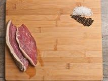 Deux biftecks fraîchement coupés en tranches sur une planche à découper en bambou avec des piles des grains de sel et de poivre d Photographie stock libre de droits
