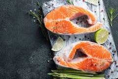 Deux biftecks frais crus saumonés ou de truite sur la glace, riche en huile omega-3, avec la chaux, le thym et la jeune asperge s photo libre de droits