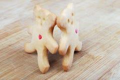 Deux biscuits faits maison sous forme de petits animaux d'ours se tenant de pair dans la perspective d'un conseil en bois Images stock