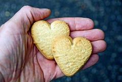 Deux biscuits secs sous forme de coeurs sur la paume Images stock