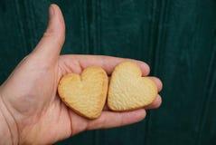 Deux biscuits secs sous forme de coeurs sur une paume sur un fond vert Photo stock