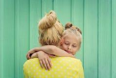 Deux blondes maman et sourire de fille, étreignant Image stock
