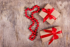 Deux boîte-cadeau avec le ruban et les perles rouges du corail rouge sur le vieux fond en bois Concept de vacances Copiez l'espac Photo stock