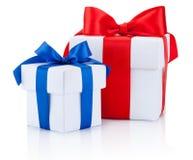 Deux boîte-cadeau blancs ont attaché bleu et les rubans rouges cintrent d'isolement sur le blanc Photographie stock