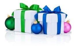 Deux boîte-cadeau blancs ont attaché des boules d'arc et de Noël de ruban vert et bleu d'isolement sur le blanc Photographie stock