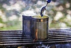 Deux boîtes de conserves étant fait cuire au-dessus d'un feu de camp, vapeur se levant, spo Image libre de droits