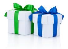 Deux boîtiers blancs ont attaché bleu et les rubans verts cintrent d'isolement sur le blanc Photographie stock libre de droits