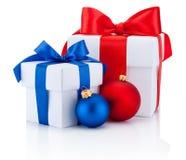Deux boîtiers blancs ont attaché des boules d'arc et de Noël de ruban rouge et bleu Photo libre de droits